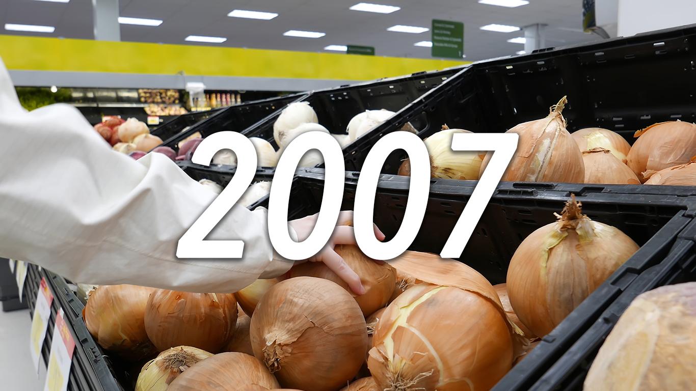 Woman picking fresh onion inside Walmart store
