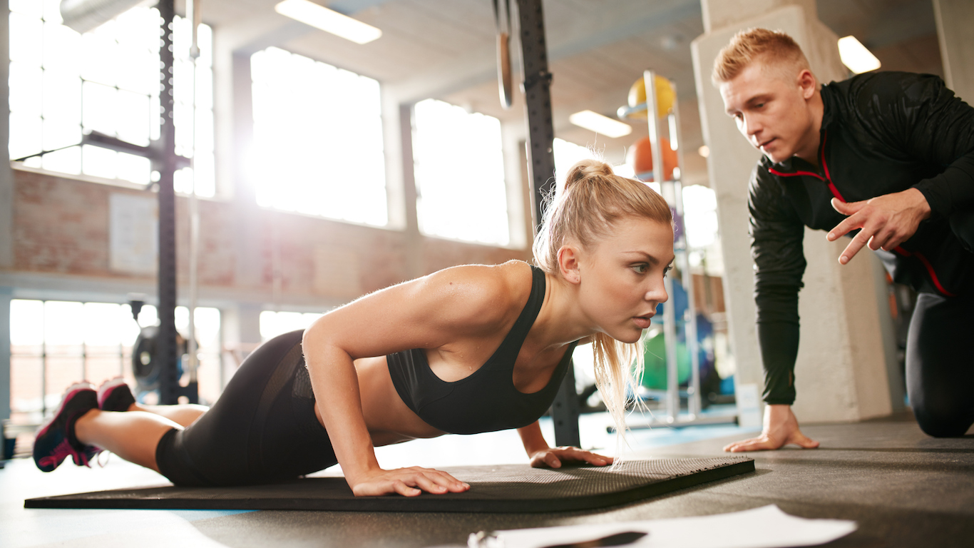 Female exercising with personal trainer at gym, sports and recreation instructor